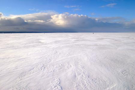 verbazingwekkende winterlandschap onder het ijs van een brede rivier en mooie wolken in de blauwe hemel Stockfoto