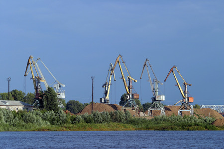 Summer landscape cranes on the river sand mining in the port photo
