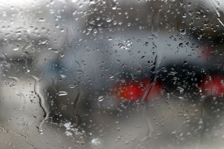 drops of condensation on the windshield of a car stuck in traffic jams on the road