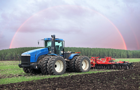 agricultural work plowing land on a powerful tractor Stock Photo