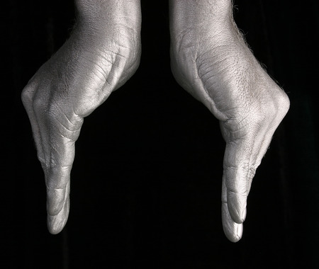 close-up of human hands represent a form of bowls or flower on black background, side view studio photo