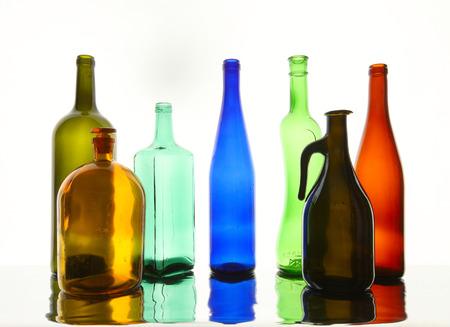 close-up schoon transparante gekleurde glazen flessen van verschillende vormen op de spiegel oppervlak in wit licht studio Stockfoto