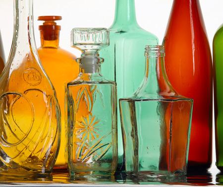 different shapes: close-up pulito bottiglie di vetro colorato trasparente di diverse forme sulla superficie a specchio in luce bianco studio