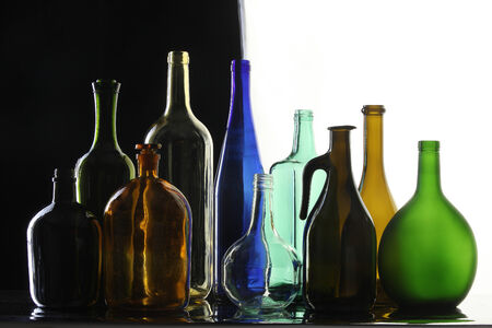 different shapes: close-up collection of beautiful colored bottles of different shapes on a black and white background studio
