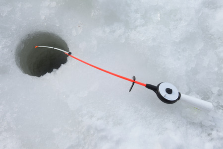 boer: close-up freshly caught fish and a fishing rod near the hole on the frozen snow-covered river cloudy day