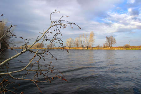 beautiful autumn landscape calm river trees without leaves and cloudy sky in sunny day photo