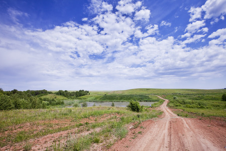 spring landscape dirt road of endless fields and beautiful clouds in the blue sky Stock Photo - 27012541