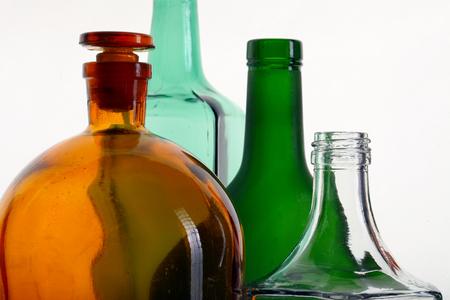 close-up of colored glass bottle necks isolated on white background studio photo