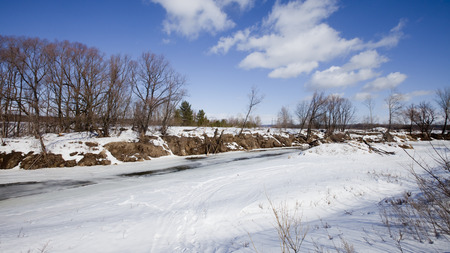 marvelous landscape in early spring on the river and white clouds on blue sky on a sunny day photo
