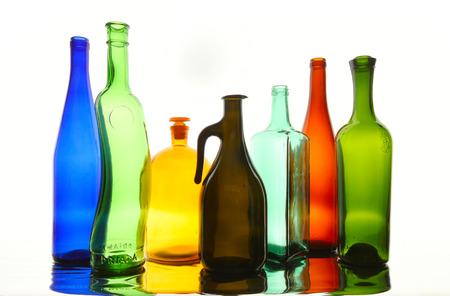 different shapes: close-up bottiglie di vetro pulite trasparenti colorate di forme diverse sulla superficie a specchio in luce bianca in studio