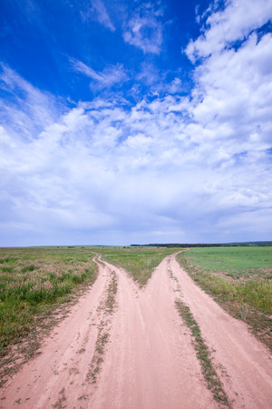 spring landscape dirt road of endless fields and beautiful clouds in the blue sky photo