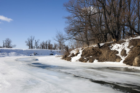 thawed: marvelous landscape in early spring on the river and white clouds on blue sky on a sunny day