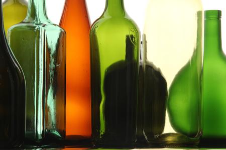different shapes: close-up bottiglie di vetro puliti trasparente colorato di forme diverse sulla superficie a specchio in luce studio bianco