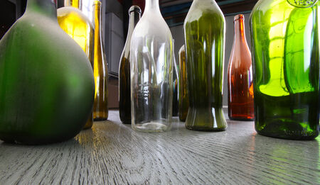 close-up colorful dusty bottles on a gray wooden floor in the studio on a background of light strip