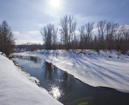early spring snow: scenic landscape river trees without leaves on the shore and the melting of snow and ice in sunny day early spring Stock Photo