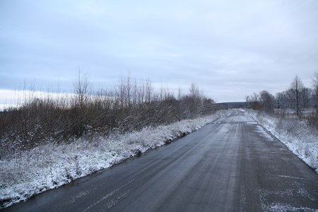 winter landscape  the first snow in field near forest and road on a cloudy day photo