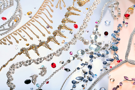 macro beautiful graceful diverse jewelry, necklaces and earrings with colored stones on white background studio photo