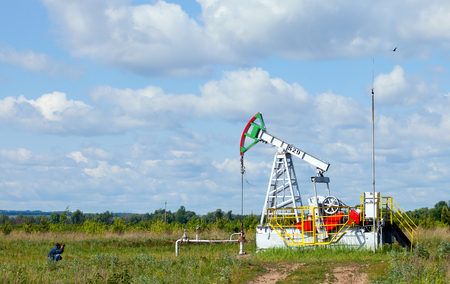 summer landscape oil pump in a green field, cloudy sky above him and the forest on the horizon photo