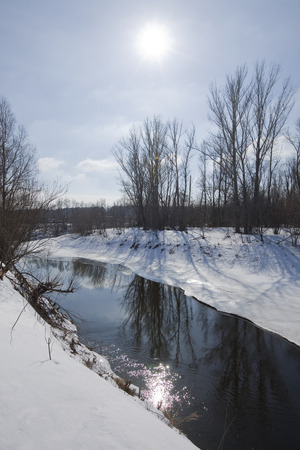 scenic landscape river trees without leaves on the shore and the melting of snow and ice in sunny day early spring photo