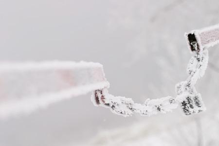 schlagbaum: Makro-Kette mit einer Sperre auf der Schlagbaum in Rauhreif auf dem Hintergrund des Flusses im dichten Nebel