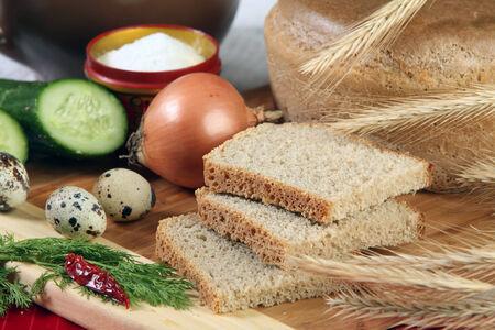 edibles: close-up di pane a fette su un tagliere e altri commestibili in studio