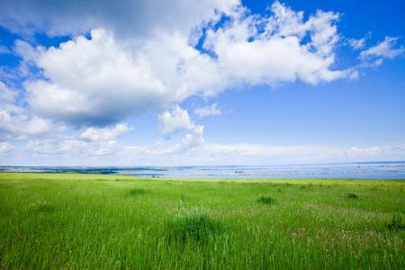zomer landschap mooie wolken in de blauwe hemel over een brede rivier op een zonnige dag