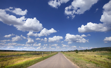 summer landscape road among fields and bright blue sky with white clouds on a sunny day Stock Photo