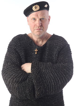 portrait of adult bald white man in black beret and chain armor on a light background studio Imagens
