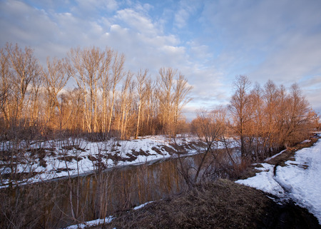 spring landscape melting of ice and snow in early spring on the river at sunset photo
