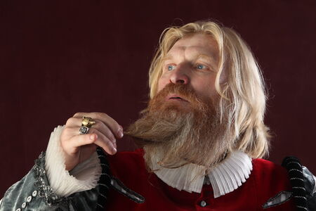 close-up portrait of an adult male with long blond hair beard and mustache in medieval costume studio on a burgundy background photo