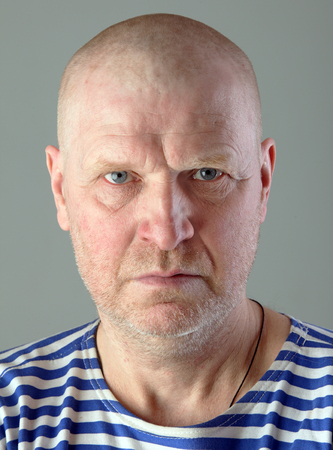 striped vest: close-up portrait of adult white bald men in striped vest  with a serious look studio Stock Photo