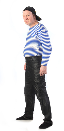 striped vest: Portrait of a adult white man in a striped vest, leather pants and a baseball cap with a serious look studio Stock Photo