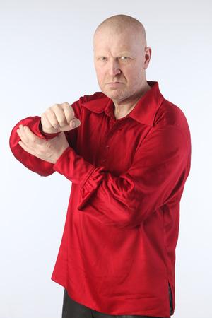 bald man: Retrato de un hombre calvo blanco adulto en una camisa roja con una cruz en el pecho en un estudio de la luz de fondo
