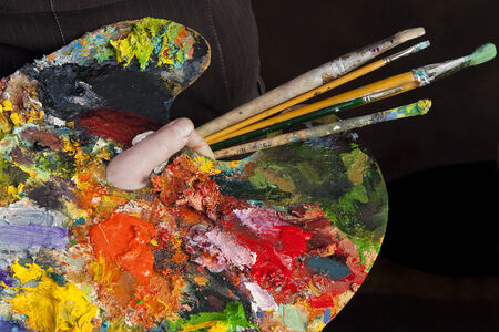 macro artist palette in hand, texture mixed oil paints in different colors and saturation studio photo