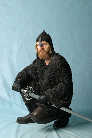 crouched: portrait of a man with a beard and mustache, a soldier in chain mail and a helmet with a sword on a light background crouched Stock Photo