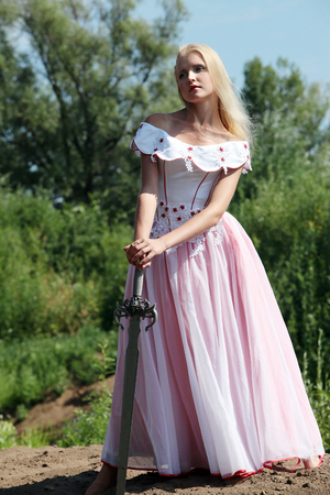 Portrait of a young romantic girl with white hair and a pink dress on a background of green grass and trees, in hands holds a sword of steel, standing at full height