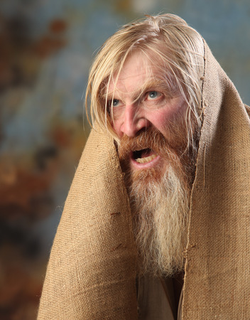 Portrait old beggar with a beard and mustache, wrapped in burlap, with pain and despair in his eyes, the studio on a brown-blue background photo