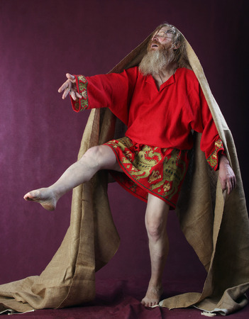 full height: portrait of the blessed with a long beard and a mustache and wet blond hair in a red shirt, with bare feet standing at full height studio