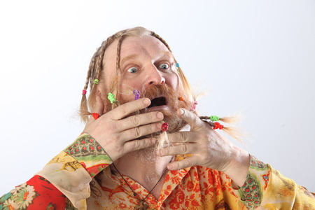 close-up portrait of an adult male with long beard, mustache and hair braided in pigtails gesturing studio on light background photo