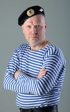 striped vest: close-up portrait of adult white men in striped vest and a black beret with a serious look studio