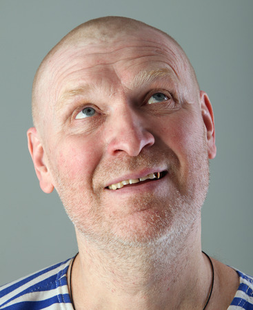 blissful: close-up portrait of the adult bald white man in a striped vest with a blissful view looking up studio