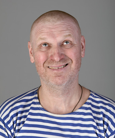 striped vest: close-up portrait of the adult bald white man in a striped vest with a blissful view looking up studio