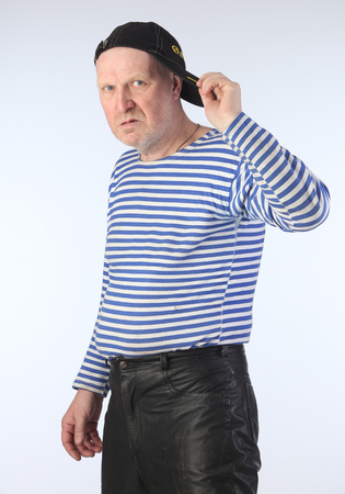 Portrait of a adult white man in a striped vest, leather pants and a baseball cap with a serious look studio photo