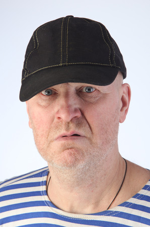 striped vest: close-up portrait of a adult white man in a striped vest and a baseball cap with a serious look studio Stock Photo