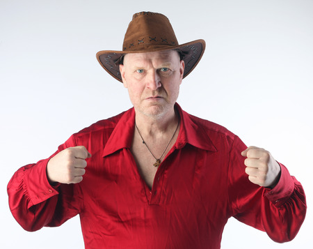 Portrait of a adult white bald man in a red shirt and cowboy hat on white background studio Imagens