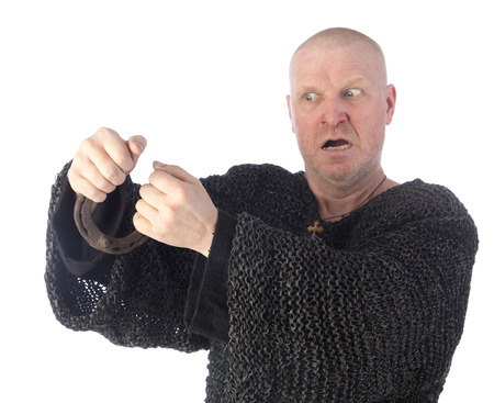 straighten: portrait of adult white men in chain armor trying with great effort to straighten a horseshoe on white background studio
