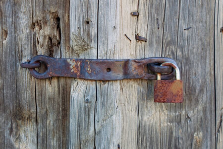 close-up of an old rusty padlock on a wooden door photo