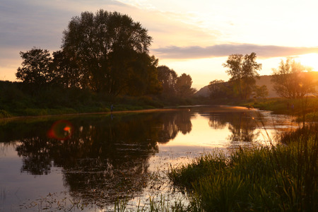 scenic landscape of sunset over a calm river and trees on the shore in the early autumn photo