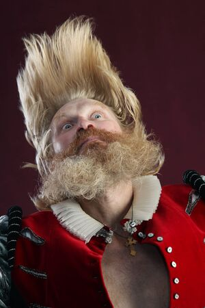 portrait of adult male with long hair beard and mustache in medieval costume tossing hair Stock Photo