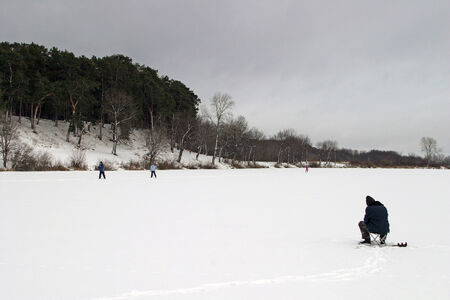 Winter landscape river covered with ice near the forest and fisherman engaged in fishing photo